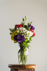 bouquet of colorful flowers in glass vase, isolated on grey