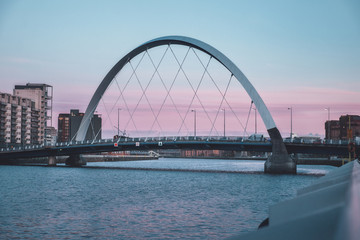 View of the Clyde Arc or Squinty Bridge from the East at sunset and river Clyde, Glasgow, Scotland