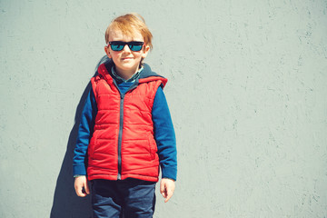 Cute stylish boy standing in front of grey wall outdoors.