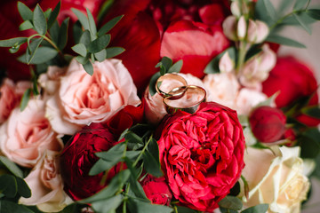two gold wedding rings lie on the bride's bouquet of red and pink roses