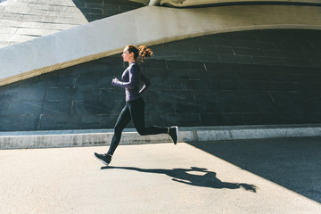 Woman jogging or running, side view with shadow