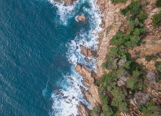 Aerial views of a coastline with waves and rocks