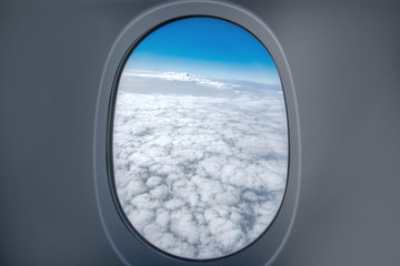 view of the cumulus clouds and the horizon in the afternoon through the plane's window.