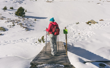 female hiker going up a mountain with snow.