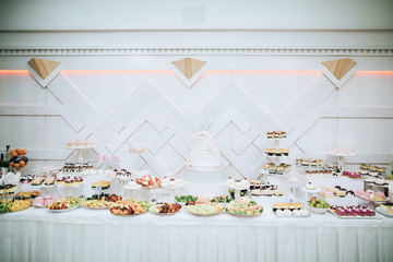 Delicious white wedding Candy bar. Table with sweets, candies, dessert