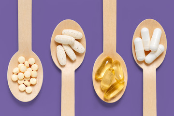 Healthy supplements on wooden spoons against purple background