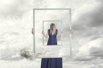 surreal image of a woman holding a frame that reflects herself