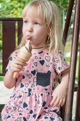 Little cute blond caucasian girl licks tongue ice cream in the summer