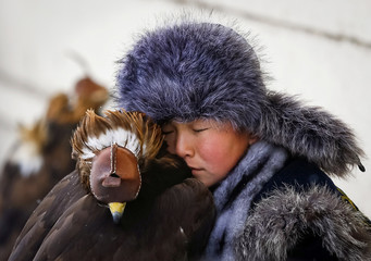 A young hunter rests next to his tamed golden eagle during an annual hunters competition at Almaty hippodrome
