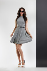 fashion portrait of a woman. young beautiful girl in gray dress and sunglasses posing in the Studio. Hand holds on to the dress