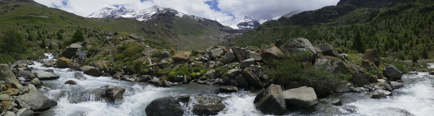 panoramic photo of mountain landscape in Valtellina, river Viola descends from the mountains in spring, Santa Caterina Valfurva, Lombardy, Italy