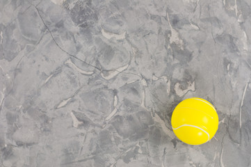 One new yellow soft rubber tennis ball on old worn cement. Top view
