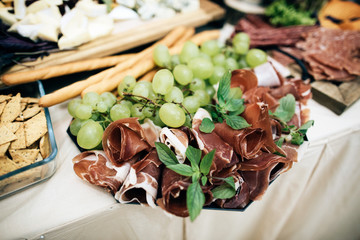Buffet table of reception with burgers, cold snacks, meat and salads, nuts, cheese