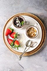 Chocolate and vanilla caramel mug cakes from microwave with fresh strawberries and spoons on round wooden tray over grey texture background. Top view, space