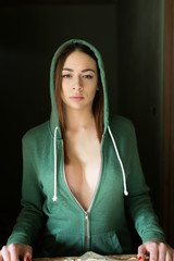 Sensual woman wearing green hoodie with prominent cleavage looking at camera