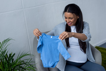 african american pregnant woman holding blue baby bodysuit while sitting on armchair