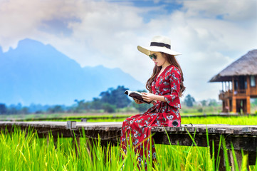Wall Mural - Young woman reading a book and sitting on wooden path with green rice field in Vang Vieng, Laos.