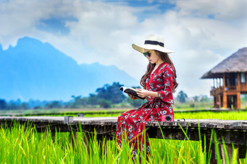 Young woman reading a book and sitting on wooden path with green rice field in Vang Vieng, Laos.