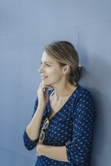 Portrait of smiling woman leaning against blue wall looking at distance