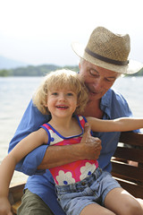 Portrait of little girl in rowing boat with her grandfather