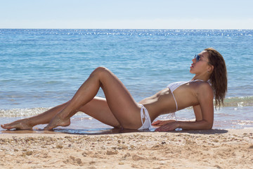 Beautiful luxury slim girl in a white bikini on the beach. Outdoor summer lifestyle image of young pretty woman outfit and sunglasses, fun ,joy, emotions.