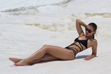 Beautiful luxury slim girl in a black bikini on the Pamukkale, Turkey. Outdoor summer lifestyle image of young pretty woman outfit and sunglasses, fun ,joy, emotions.
