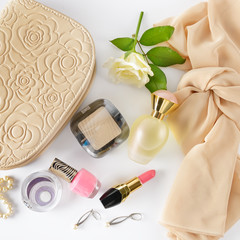 Cosmetics, perfumes, jewelry made of pearls and handbag on a white background.