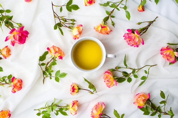 Orange roses and a tea cup on white fabric