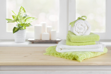 Spa towels on wooden table over blurred salon window background