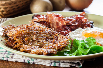 Hash browns. Potato pancakes with crispy fried bacon and fried egg