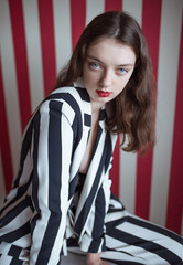 Sexy young woman in stylish striped suit posing on red background. Vogue fashion style
