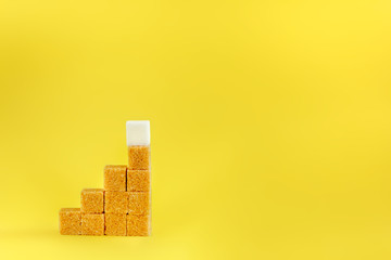 Sugar cubes on a yellow background - concept of growth. Copy space