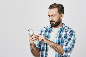 Portrait of attractive guy with beard and moustache holding smartphone and browsing network with surprised and perplexed expression, standing against gray background. Husband just got anxious message