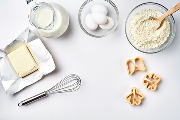 Objects and ingredients for baking, plastic molds for cookies on a white background. Flour, eggs, whisk, milk, butter, cream. Top view, space for text