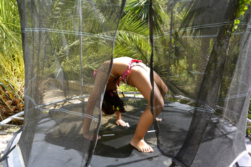Girl doing gymnastic exercises on a trampoline