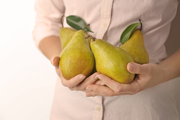 Woman holding ripe pears on light background, closeup