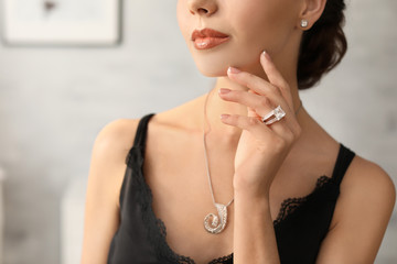 Beautiful young woman with elegant jewelry indoors, closeup