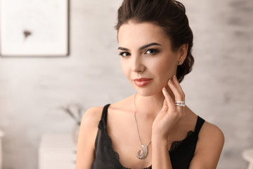 Beautiful young woman with elegant jewelry indoors