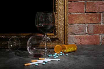 Alcohol, drugs and cigarettes on table near brick wall