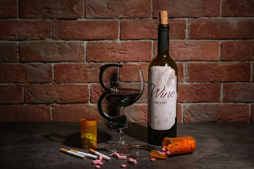 Composition with alcohol, drugs, cigarettes and handcuffs on table near brick wall