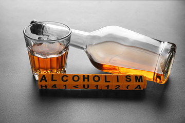 "Bottle and glass of alcohol with word ""Alcoholism"" on grey background"