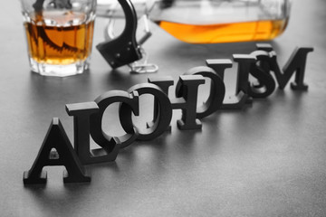 "Composition with alcohol, handcuffs and word ""Alcoholism"" on grey table"