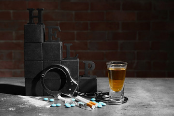 "Composition with word ""Help"", drugs, alcohol, cigarettes and handcuffs on table"