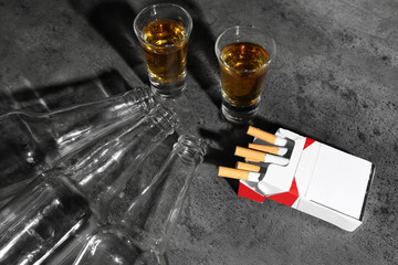 Alcohol and cigarettes on grey background