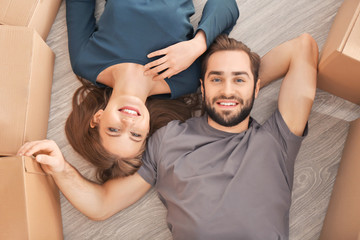 Happy young couple lying on floor in their new home near moving boxes
