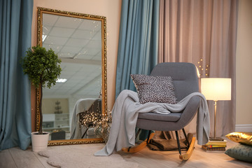Elegant room interior with comfortable rocking chair and mirror