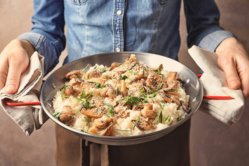 Woman holding dish with delicious risotto and mushrooms, closeup
