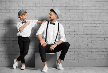 Father and son in elegant suits against brick wall