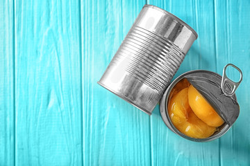 Cans with pickled apricots on wooden background