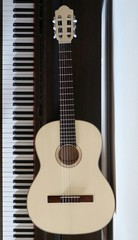 Light wood acoustic guitar next to the piano keyboard